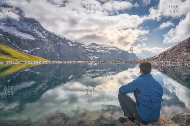 Back view of anonymous male tourist admiring magnificent lake with pure water surrounded by ridge and reflecting sky with clouds in daylight