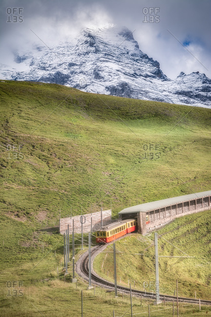 Spectacular view of mounts covered with grass and tram on rails under snowy ridge and cloudy sky in daylight