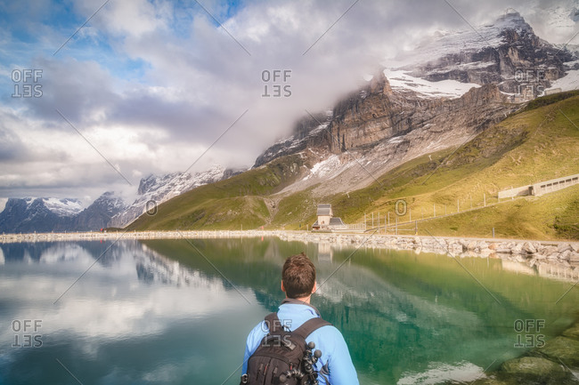 Back view of anonymous male tourist with backpack admiring magnificent lake with pure water surrounded by ridge and reflecting sky with clouds in daylight and with railway leading to house on shore near rough rock