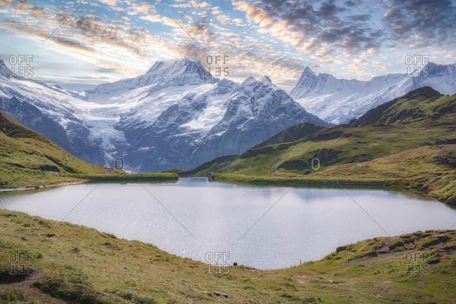 Breathtaking view of small pond with rippled water surrounded by green hills and snowy ridge under blue sky with clouds in afternoon