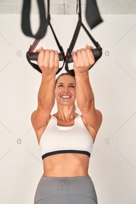 Strong positive woman in comfortable sportswear doing exercise on  suspension straps while training in gym