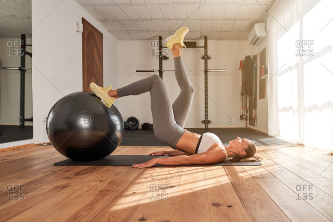 Slim female athlete lying on sports mat and doing hip thrusts with one leg on fit ball training stability