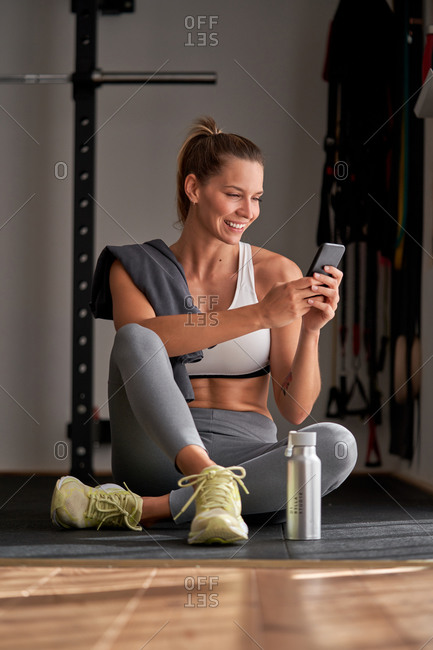 High angle of calm woman in sportswear sitting on floor with bottle of water and browsing smartphone after training