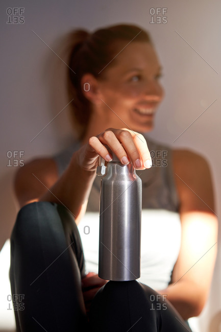 Crop anonymous sportswoman with metallic bottle of water resting after intense workout in fitness center