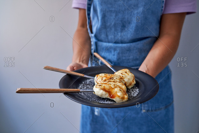 Unrecognizable female cook in apron standing at home with plate of delicious creme brulee with browned sugar