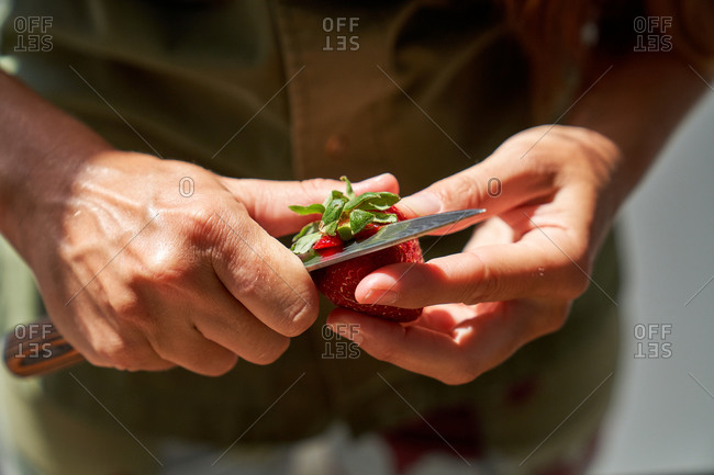 High angle of female cook peeling fresh strawberry while preparing ingredients for homemade cake in kitchen