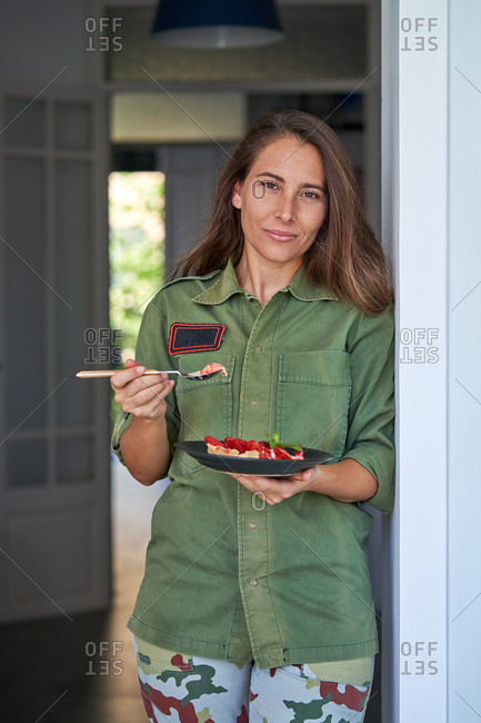 Cheerful female standing with piece of palatable homemade strawberry pie on plate and looking at camera