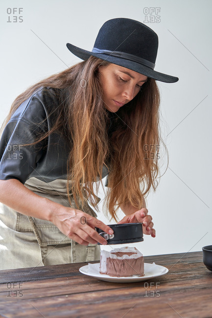 Focused female in stylish hat and apron removing cake from baking form while preparing dessert in kitchen