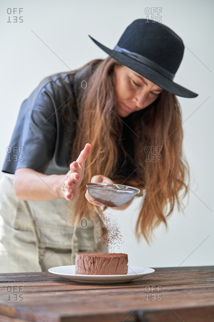 Young female in trendy hat and apron sprinkling chocolate cheesecake with cocoa powder while preparing delicious dessert in kitchen