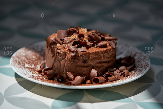 Closeup of palatable chocolate cheesecake sprinkled with cocoa powder and decorated with chocolate shavings served on white plate