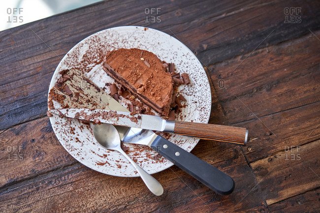 From above of cut piece of chocolate mousse cake sprinkled with cocoa powder served on plate with spoon and knife with spatula
