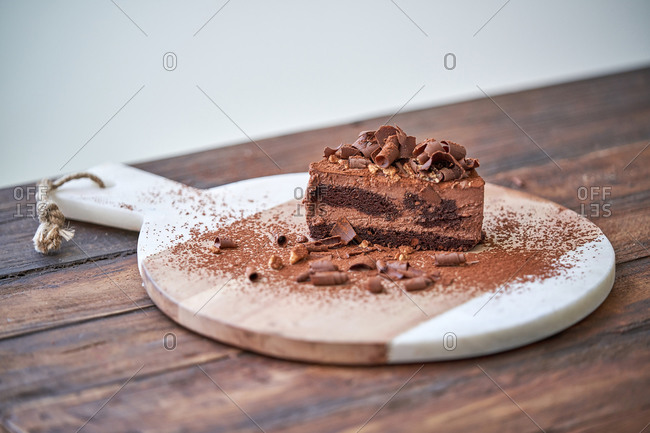 Delectable halved chocolate mousse cake served on wooden board on table
