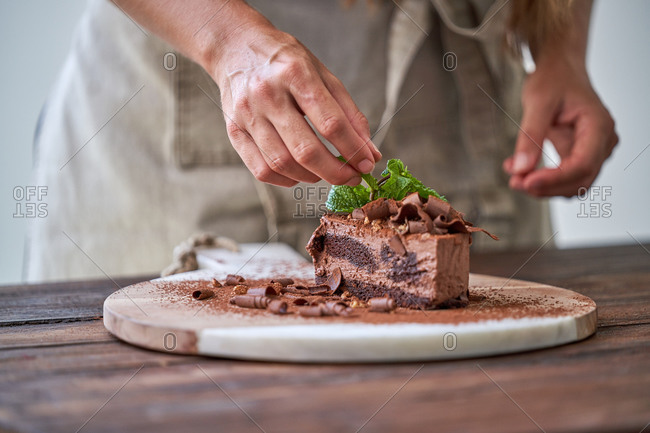 Crop anonymous female chef decorating appetizing halved chocolate cake with fresh mint leaves