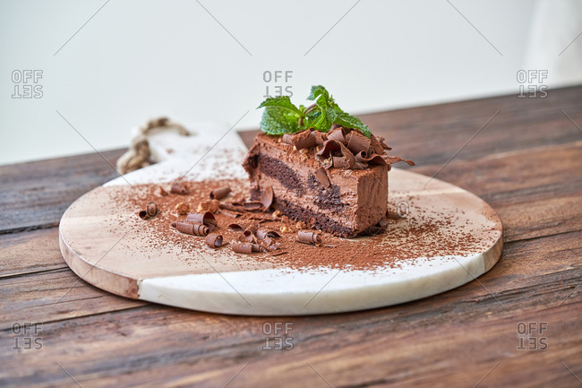Delectable halved chocolate mousse cake with garnished with fresh mint leaves served on wooden board on table