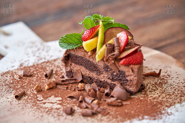 Delectable halved chocolate mousse cake with garnished with fresh mint leaves and fruits with berries served on wooden board on table