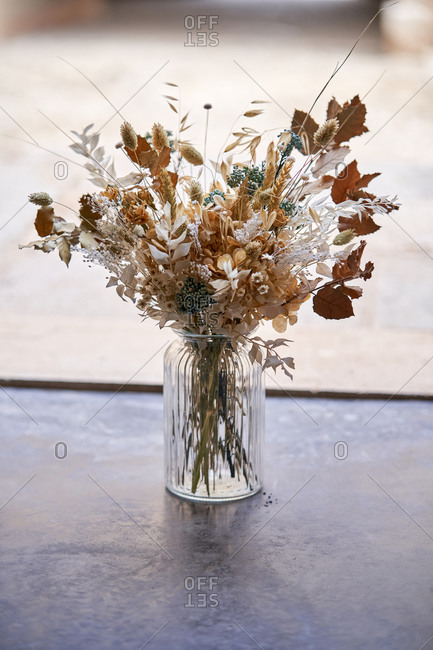 Bunch of various dried flowers and plants in glass vase placed on concrete floor