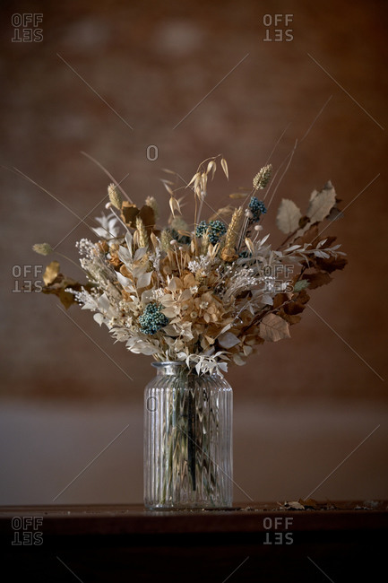 Bunch of various dried flowers and plants in glass vase