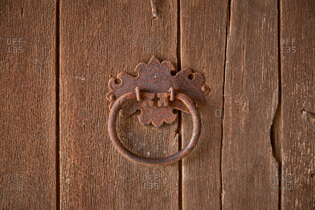Closeup of detail of shabby wooden door with old rusty knocker with round handle during daytime in countryside