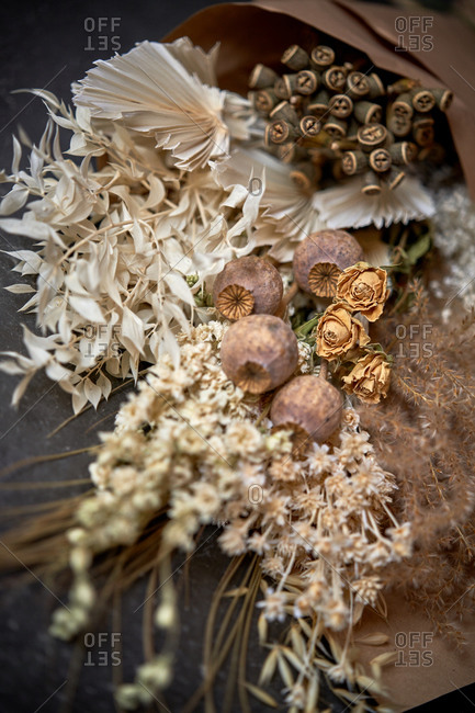 From above of bunch of dried flowers wrapped in craft paper and placed on table