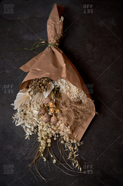 From above of bunch of dried flowers wrapped in craft paper and placed on shabby table