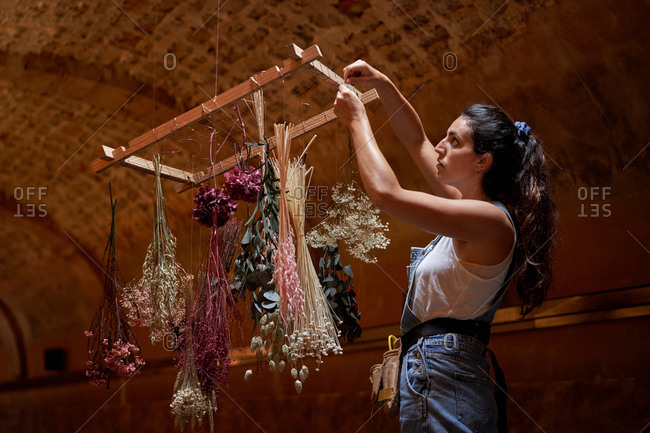 Side view of female standing on stool and preparing flowers for drying while hanging bouquets under ceiling in aged building