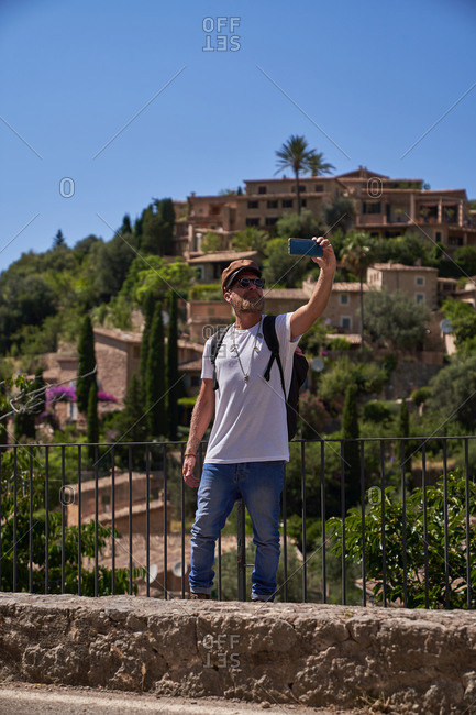 Cheerful hipster bearded male tourist in stylish sunglasses and cap taking selfie on smartphone while visiting historic settlement during summer trip