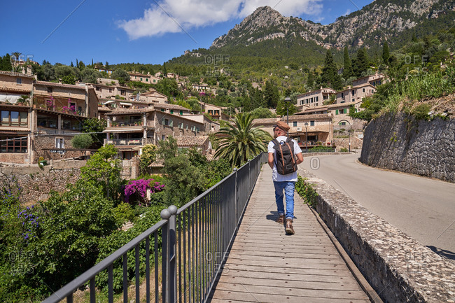 Full length back view of anonymous male tourist with backpack walking on bridge in old town located in green hills in summer day