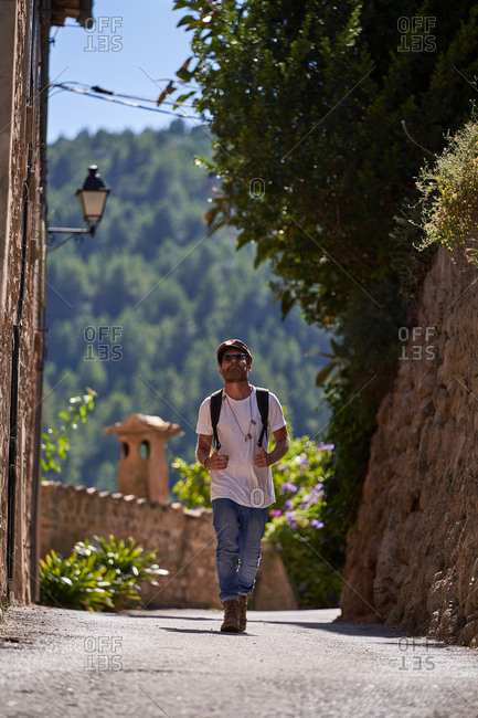 Full length of stylish bearded male tourist in trendy outfit and sunglasses with backpack walking on bridge in old town located in green hills in summer day