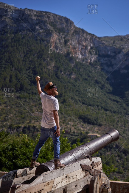 Back view of excited bearded male tourist in stylish clothes standing with arm raised on ancient cannon against mountains during summer travel
