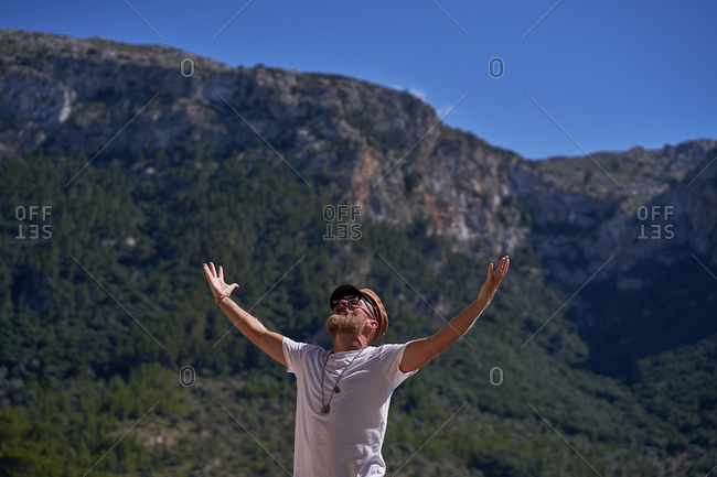 Bearded male tourist with raised arms against mountains during summer travel