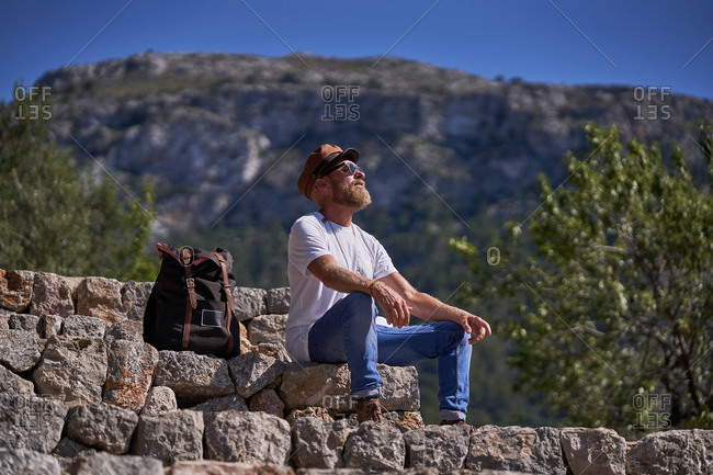 Low angle of calm hipster male backpacker in stylish wear sitting on stony fence against blurred mountains while resting during trekking in summer day