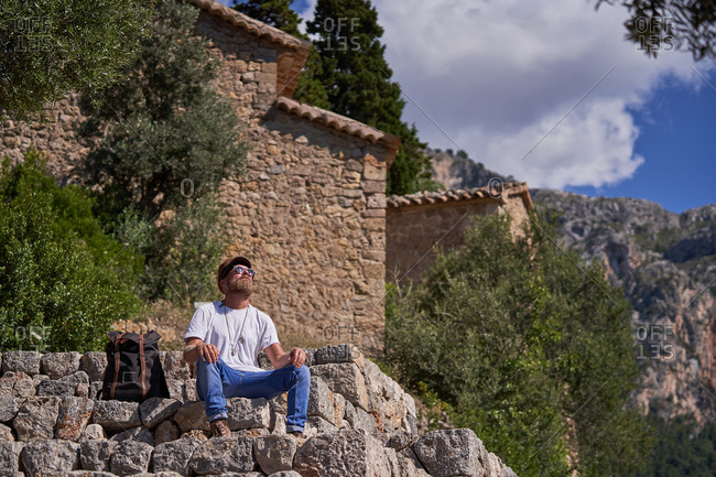 Contemplative hipster male backpacker sitting on stone border near ancient houses and enjoying views while spending summer holidays in mountainous terrain