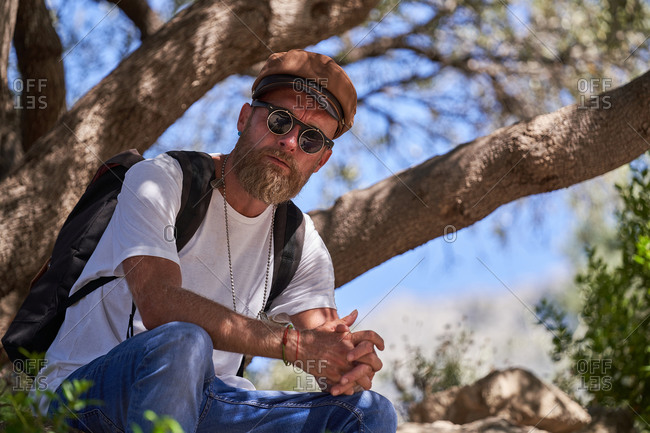 Low angle side view of contemplative adult hipster male traveler in cap and sunglasses with backpack relaxing under tree branches looking at camera during hiking in nature in sunny summer day