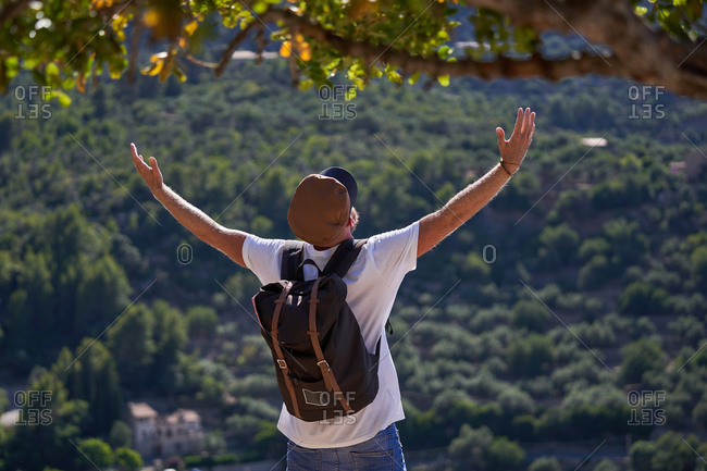 Back view of unrecognizable male hiker in cap with backpack standing with outstretched hands on hill against green forest and enjoying freedom during summer adventure