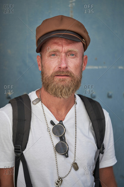 Adult bearded male hiker in trendy outfit and cap with stylish accessories and backpack looking at camera against blurred gray wall