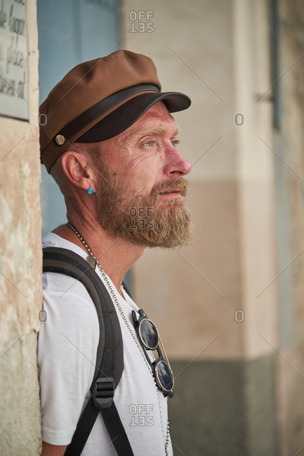 Side view of Adult bearded male hiker in trendy outfit and cap with stylish accessories and backpack looking away outdoors