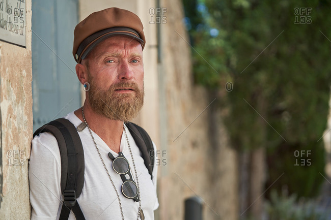 Adult bearded male hiker in trendy outfit and cap with stylish accessories and backpack looking at camera outdoors