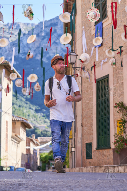 Full body adult hipster male traveler with backpack walking on street with colorful decorations in old town during summer holidays