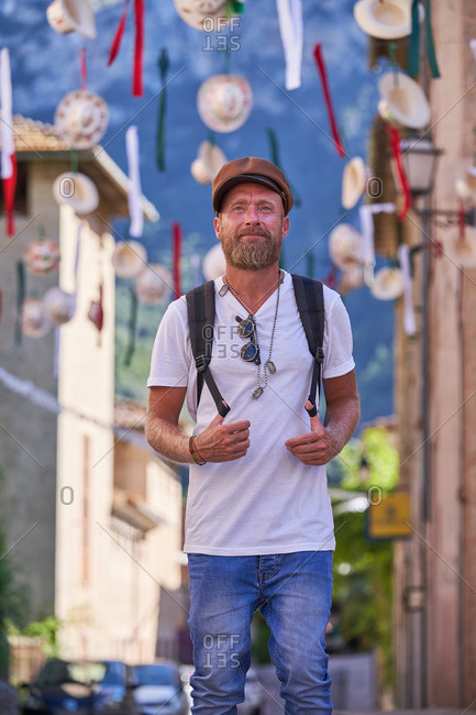 Adult hipster male traveler with backpack walking on street with colorful decorations in old town during summer holidays