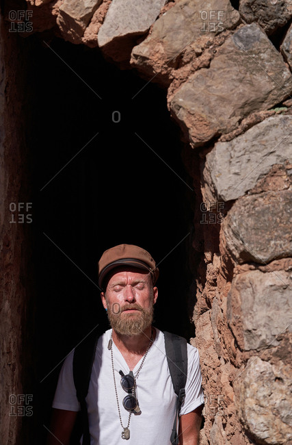 Adult bearded male tourist in trendy clothes with backpack standing in arched doorway of ancient stone building while visiting old town during summer vacation