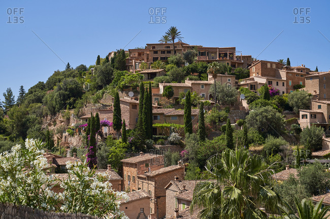 Picturesque view of ancient settlement with small stone houses located on green hill against cloudless blue sky in sunny summer day