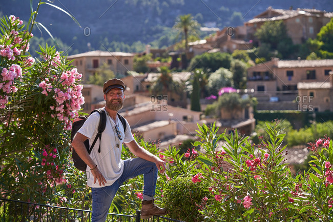 Side view of hipster male tourist in stylish outfit with backpack standing near fence with blooming bushes and enjoying picturesque scenery of old town located among green hills in summer day
