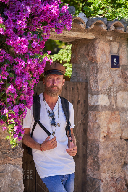Serious middle aged hipster male in trendy clothes with backpack standing near weathered stone wall with wooden door and blooming plants while visiting old town