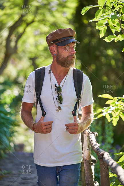 Bearded hipster male hiker in stylish clothes and cap with backpack walking along wooden fence on narrow pathway in green forest in sunny summer day