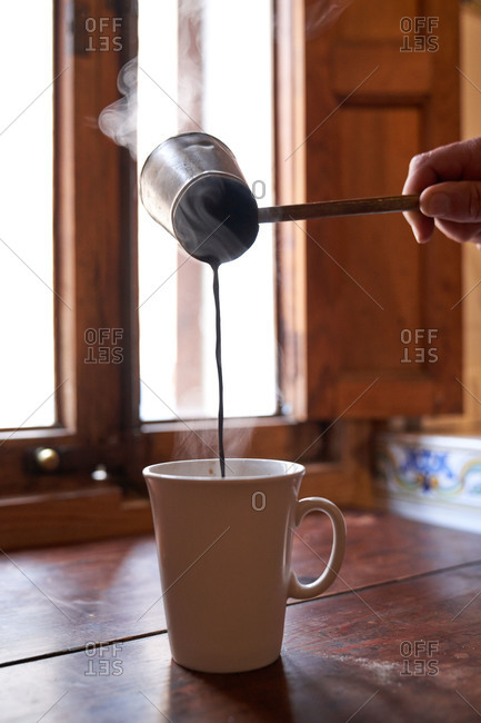 Faceless person with cezve pouring aromatic hot beverage in mug placed on wooden table at home