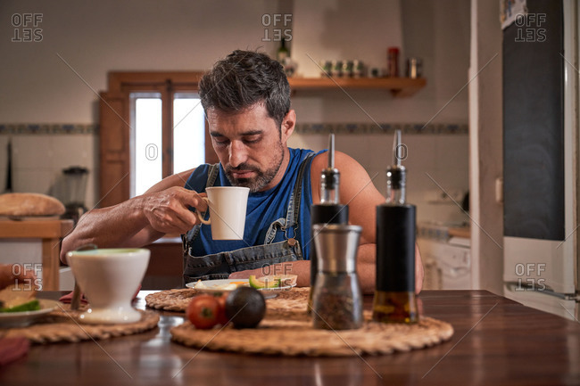 Calm male sitting at table in kitchen drinking fresh hot beverage in a mug and enjoying tasty breakfast