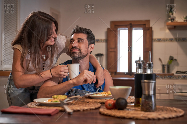 Happy husband and wife hugging at table and looking at each other during delicious breakfast in morning