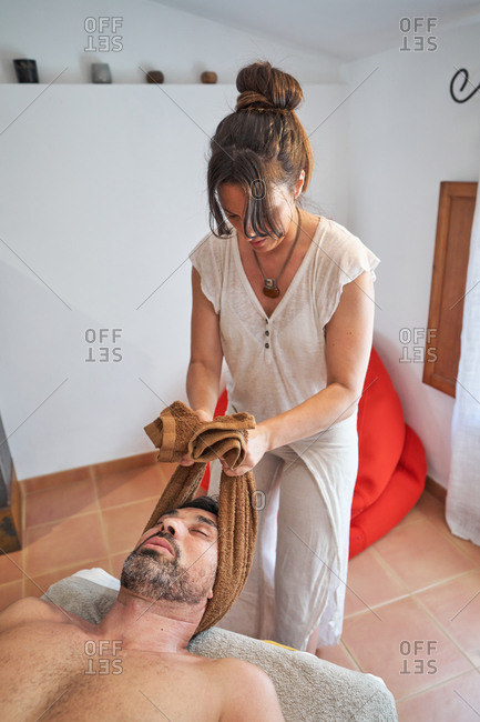 High angle of busy female therapist kneading neck of male client with towel in modern salon