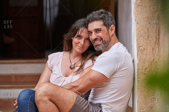 Delighted wife and husband sitting on stairs in city and embracing while looking at camera and enjoying weekend together