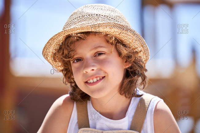 Positive little boy with curly hair in straw hat looking at camera with toothy smile while sitting outdoors